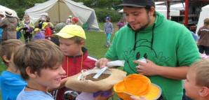 Ein Mitarbeiter der Kinderspielstadt hält den Kindern einen Strohhut hin.