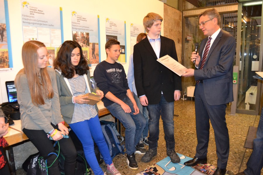 Die Forschungs-AG des Listgymnasiums hat ein Gerät entwickelt, das Handys beim Laufen auflädt: Bürgermeister Alexander Kreher überreicht dafür einen Förderpreis.