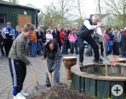 Zwei Schuler der Morgensternschule und ihr Lehrer Herr Blankenhorn pflanzen den Baum und bedecken ihn mit Erde