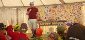 Ein junger Mann moderiert auf einer Bühne die Produktversteigerung am letzten Tag der Kinderspielstadt.
