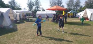 Kinder stehen auf dem Marktplatz von Burzelbach: ein Sonnenschirm der von Zelten umgeben ist