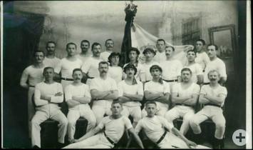 Turnmänner des Turnerbundes als Teilnehmer des Kreisturnfestes 1912 auf einer Atelieraufnahme mit Fahne.