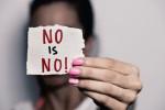 """Frau hält einen Zettel mit dem Text """"No is no"""""""