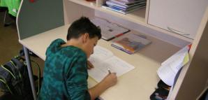 Schüler erledigt Aufgaben an einem Schülerarbeitsplatz