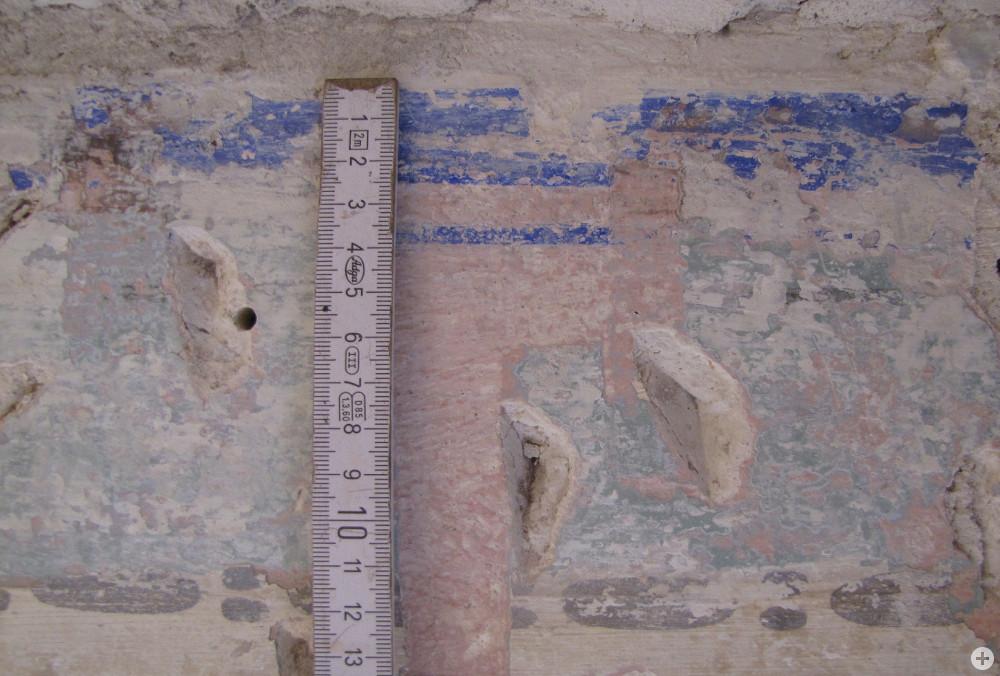 Ein Meterstab an einer Wand mit blauer Markierung