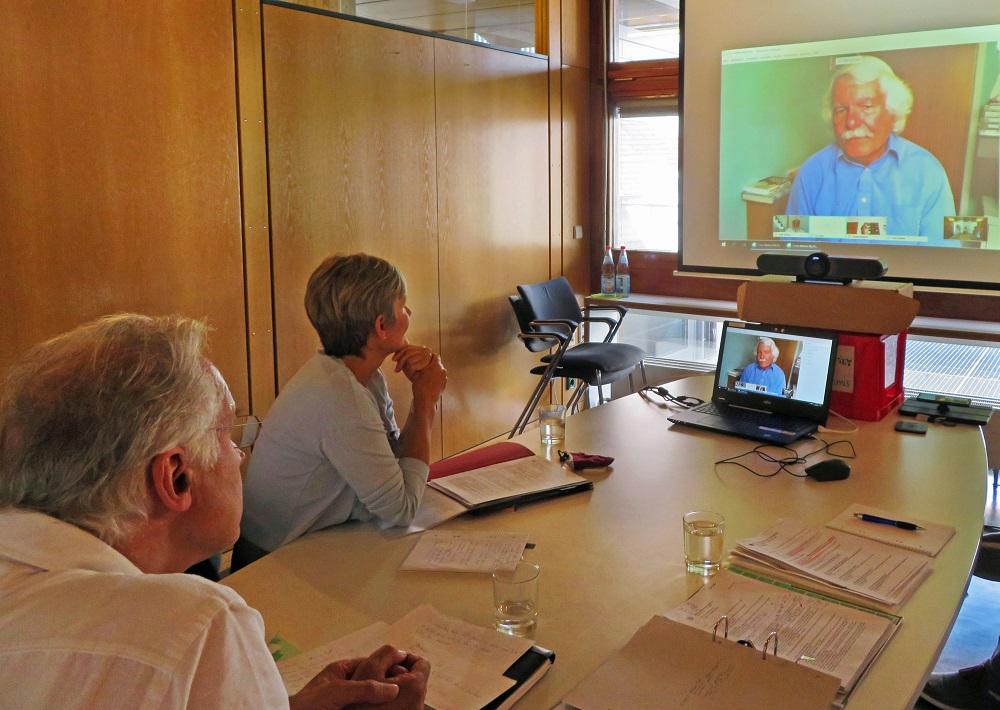 Videokonferenz mit Ellesmere Port – Zwei Personn sitzen an einem Tisch vor einem Beamer auf der die Konferenz übertragen wird