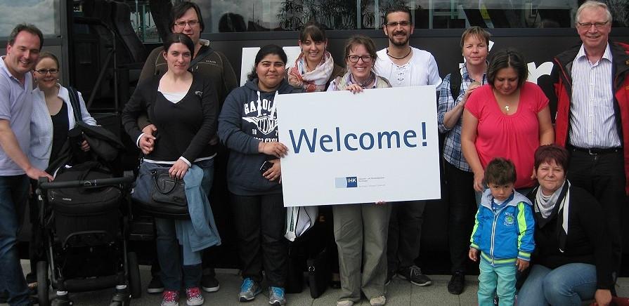 """Eine Gruppe Menschen steht vor einem Bus. Eine Dame in der Mitte hält ein Schild mit der Aufschrift """"Welcome!"""""""