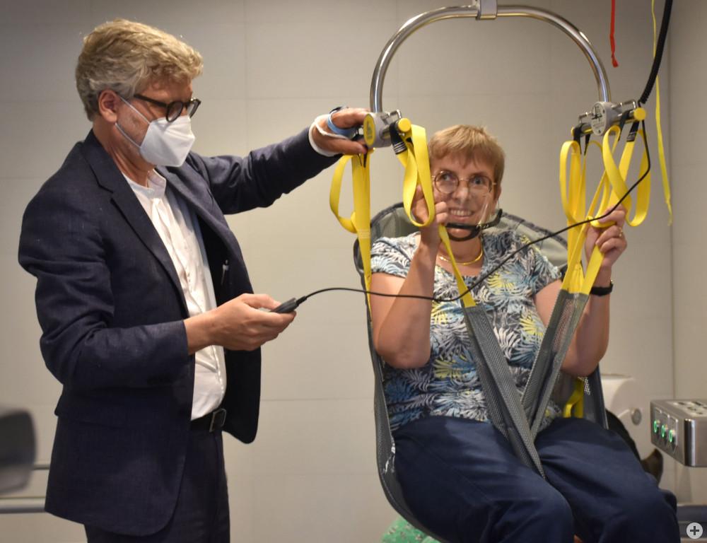 Bürgermeister Kreher bedient den Lift in der Toilette für alle, in dem Jutta Pagel-Steidl sitzt.