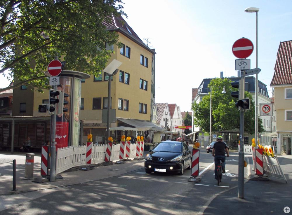 Ein Fahrradfahrer fährt auf dem neuen Fahrradschutzstreifen in der Metzgerstraße. Daneben hält ein Auto an einer Ampel.