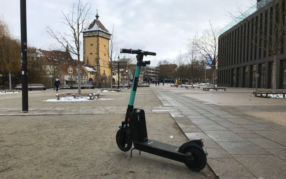 Ein schwarzer E-Scooter steht im Bürgerpark. Im Hintergrund: Stadthalle und Tübinger Tor