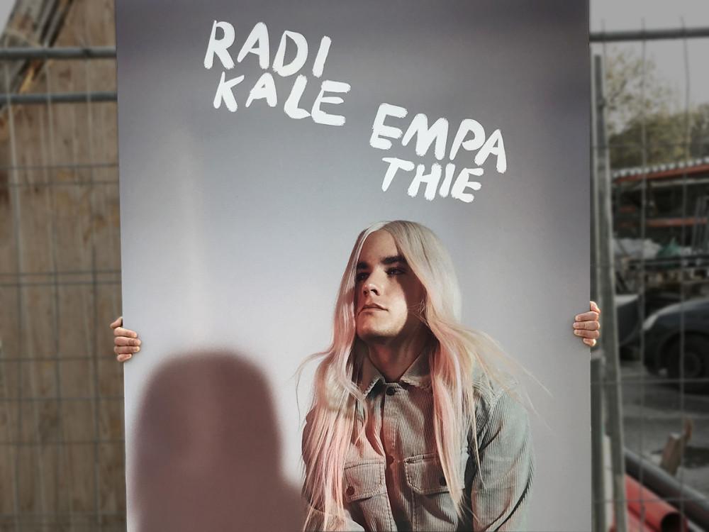Eine Person mit blonder Perrücke sitzt vor einem Poster mit der Aufschrift RADIKALE EMPATHIE_Pressebild_PPG_Containercity_BRE