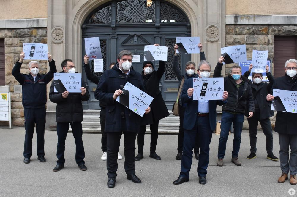 """Die Akteure, die sich an der Luca-App in Reutlingen beteiligen, halten Plakate mit der Aufschrift """"Wir machen mit"""" hoch."""