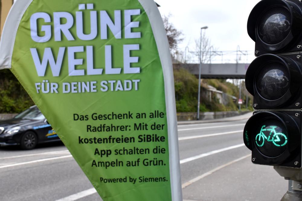 """Eine grüne Fahrrad-Ampel. Im Hintergrund eine Beachflag mit dem Titel """"Grüne Welle für deine Stadt"""""""