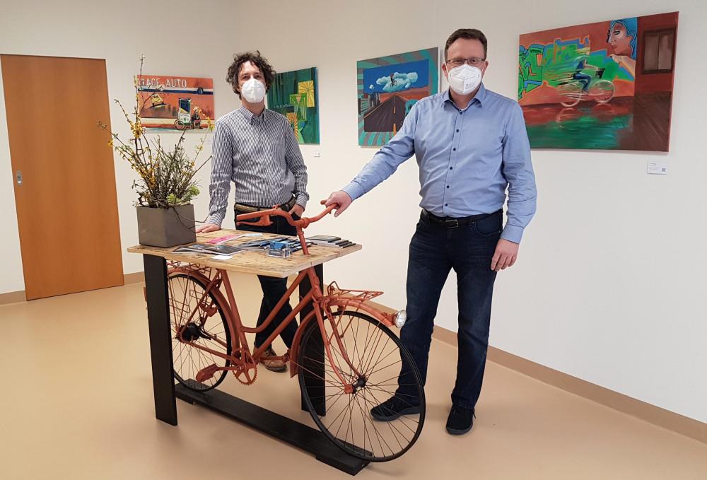 Dr. Carsten Hutt und Markus Flammer stehen an einem Tisch, an den ein Fahrrad lehnt, in der Galerie des Wechselnden Wilhelm