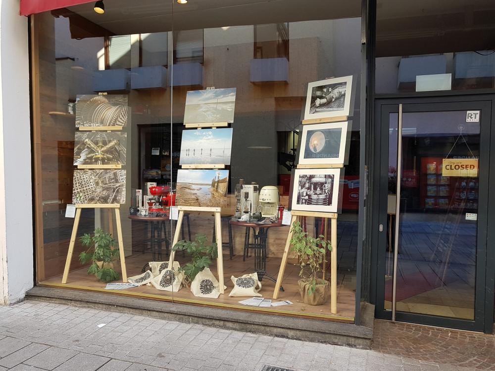 Neun Bilder der Fotoausstellung auf drei Staffeleien in einem Schaufenster