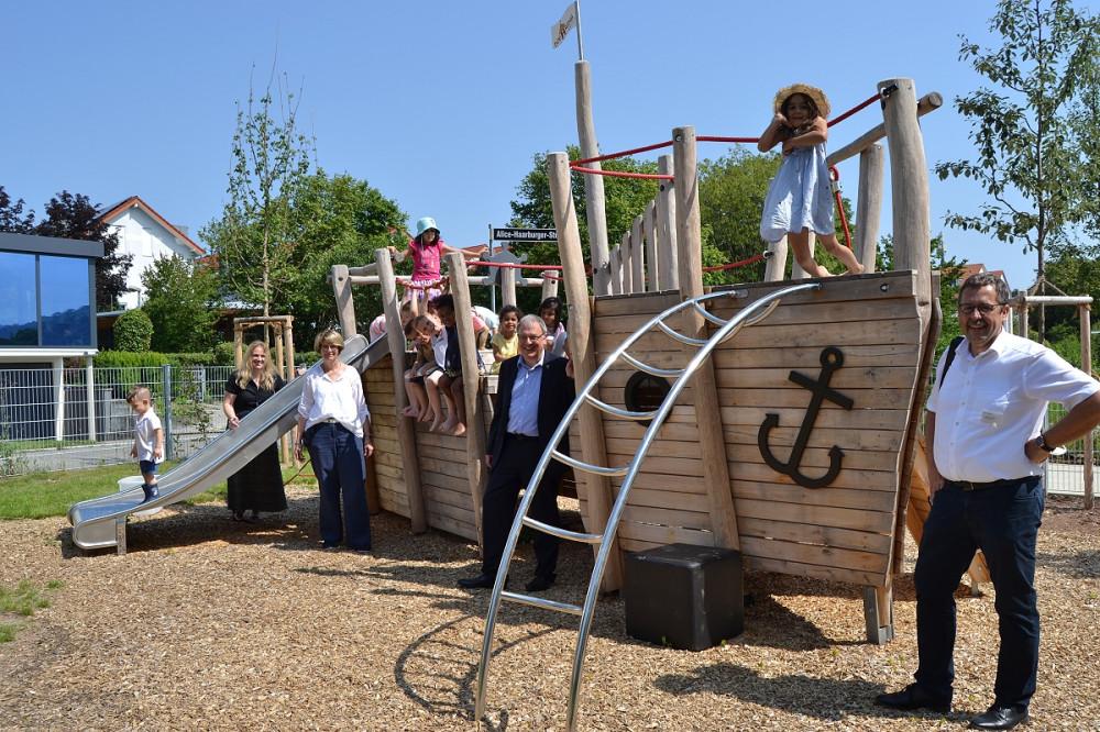 Zahlreiche Kinder sind auf dem Spiel-Schiff im Außenbereich des Kinderhauses zu sehen, zusammen mit den Erzieherinnen, OB Keck und Sozialamtsleiter Joachim Haas