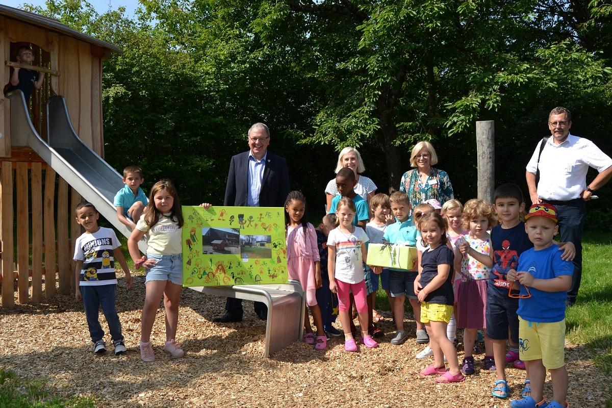 OB Keck beim Besuch des Kinderhauses Aachener Straße am Spielgerät mit Kinder und Erzieherinnen