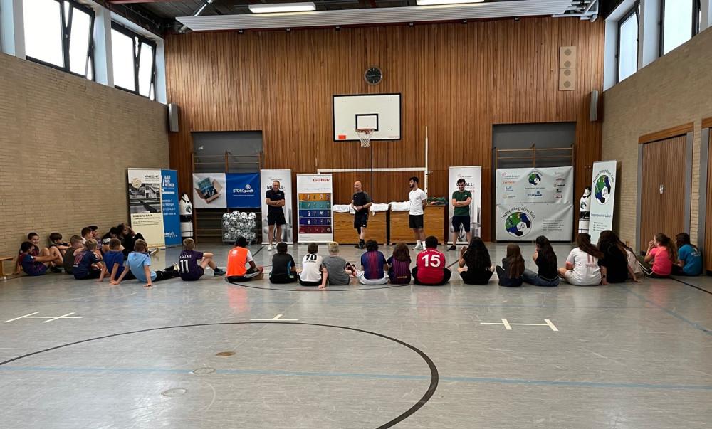 Mehrere Kinder in Sportkleidung sitzen auf dem Boden der Sporthalle und hören den Anweisungen der Fußballtrainer zu.