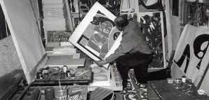 """""""Atelier und Werkstatt"""" – HAP Grieshaber präsentiert seine Arbeiten      Das Fotohaus Dohm machte im März 1959 eine Bildreportage über den immer bekannter werdenden Reutlinger Künstler. Grieshaber präsentierte dem Fotografen seine Werke im Atelier an der Achalm. Hier zeigt er gerade einen Druck aus seiner """"Baby-Serie"""", die nach der Geburt seiner Tochter Ricca 1954 entstanden war. Auch die zahlreichen Tiere aus seinem """"Hauszoo"""", wie beispielsweise hier die Katze, tauchen immer wieder als Motiv in seinen Werken auf.    StadtA Rt., S 105/5 Nr. 3987/9a"""