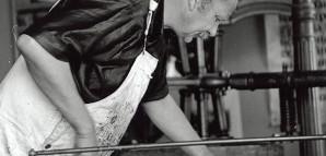 """""""Der Drucker"""" – HAP Grieshaber an der Druckerpresse  Grieshaber war ein Vertreter der Volksbildung. Die Reproduktionstechnik  beim Holzschnitt machte Kunst bezahlbar und so konnten sich immer mehr Menschen ein Bild für die eigene Wohnung leisten. Grieshaber arbeitete mit einer alten Handdruckpresse, die er im Sommer 1963 dem Fotografen vorführte. Auch das Motiv des Handdruckers hat er in seinen Werken verarbeitet.     StadtA Rt., S 105/4 Nr. 9199/5"""