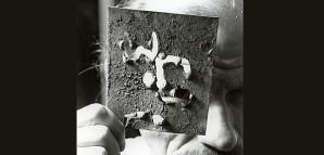 """""""Geheimnisvolle Identitäten"""" – HAP Grieshaber hinter Maske   Der Künstler liebte Inszenierungen, Verkleidungen und geheimnisvolle, mehrdeutige Aussagen. Abstrakte Kunstobjekte und an exotischen Vorbildern orientierte Masken nutzte er beim spielerischen Dialog mit Kamera, Fotograf und Betrachter. """"Eulenspiegel aus Schwaben"""" nannte ihn der Schriftsteller Werner Steinberg, der in der Nachkriegszeit in Reutlingen lebte. Die Aufnahme entstand vermutlich um 1960.  StadtA Rt., S 105/4 Nr. 16137 FB3"""